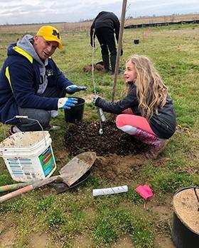 Un membre et sa fille plantent un arbre durant une action du club.